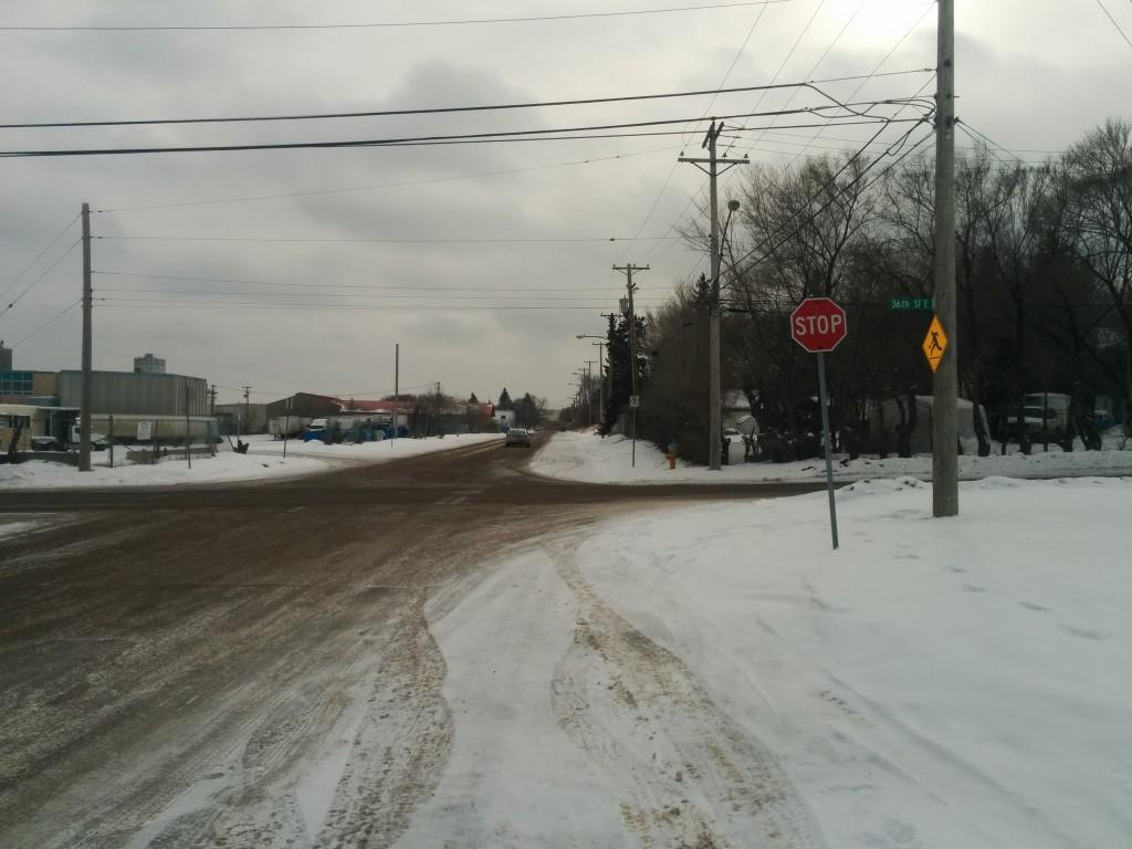 """The Full Saskatoon"" a street with a park and a school but no sidewalks."